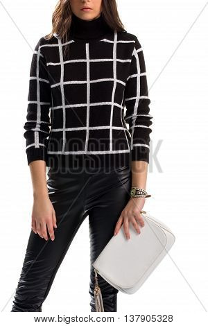 Lady holds white clutch bag. Black pants and checkered sweatshirt. New stylish wear. Quality leather and cotton.
