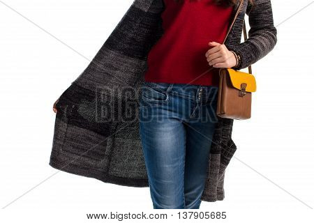 Long striped sweater coat. Girl in blue jeans. Woolen outerwear and leather bag. Combination of dark and light.