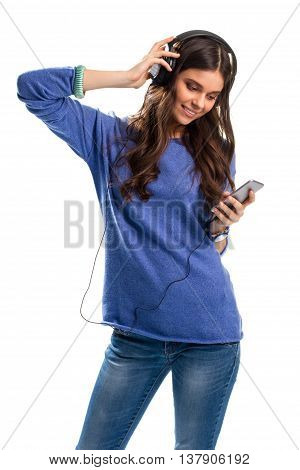 Smiling girl in headphones. Lady holds a cell phone. Casual clothes and electronic gadget. Check out the sound quality.