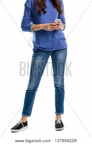 Lady in pullover holds phone. Simple blue jeans and shoes. New smartphone from famous brand. Technology is our best friend.