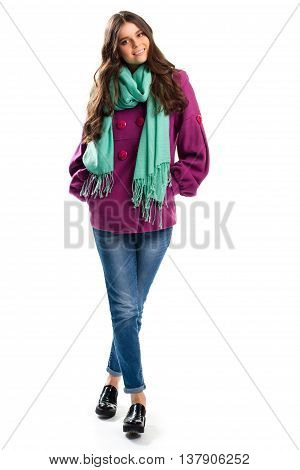 Smiling woman in purple coat. Denim pants and turquoise scarf. Autumn outfit with black shoes. Clothes of cotton and fleece.