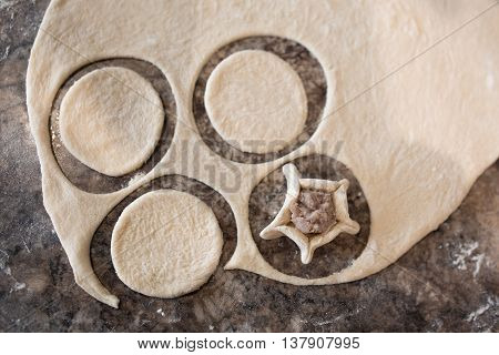 Prepare raw homemade russian food - dumpling. Their in flower and have form of star. Pork chicken mincemeat. Background table in kitchen.