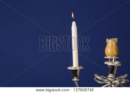 Candlestick with burning candle on blue background.