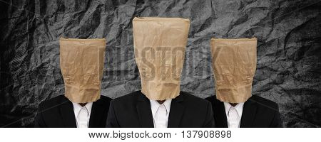 Group of businessman with brown paper bag on head on black crumpled texture