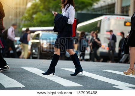 Businesswoman walking on crosswalk and texting on smartphone in city street