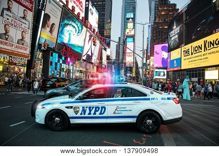 NEW YORK CITY MAY 12: NYPD police squad car goes to emergency call with alarm and siren light in the Time Square streets of New York City New York United States on May 12 2016