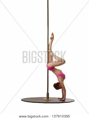 Pole dance. Red-haired woman doing handstand, isolated on white