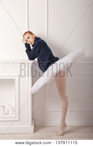 Pretty young ballerina grieves fireplace. A girl wearing a tutu and a black sweater.