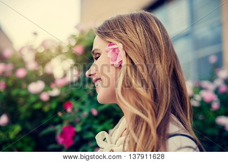 Happy beautiful woman smiling and walking on the street with flower in her hair and enjoying the life