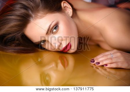Portrait of beautiful girl with trendy makeup lying