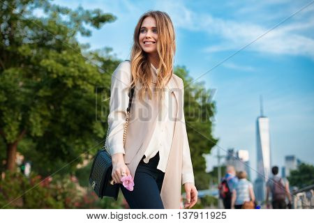 Beautiful happy young woman walking in the city park and looking to the side