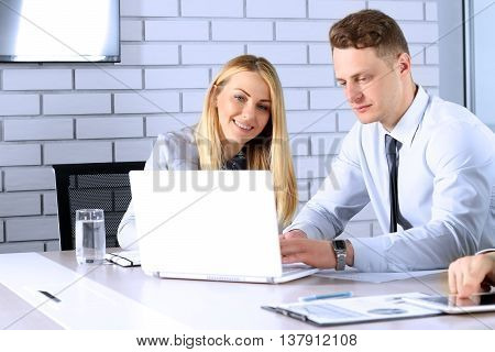 Business colleagues working and analyzing financial figures / graphs on a laptop