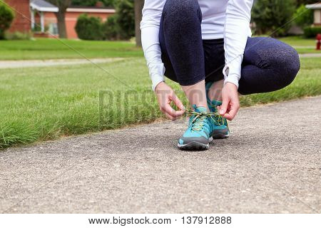 young woman runner tying shoelaces. Green background behind