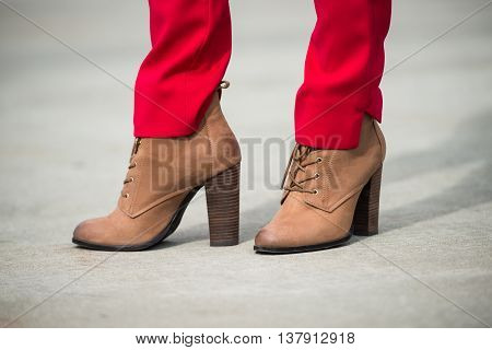 Woman wearing red pants and brown leather high heel shoes in old town