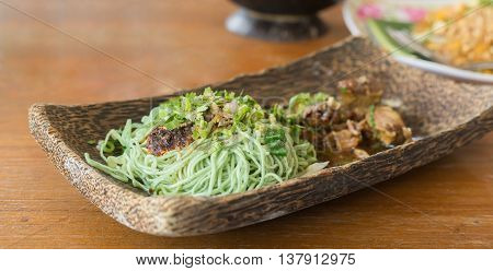 spicy green noodles on wood plate thai style