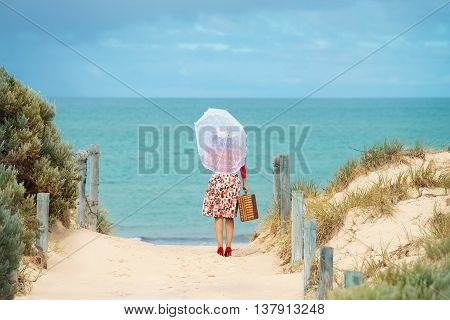 Beautiful woman traveler in retro style dress on the beach. Local focus on the woman
