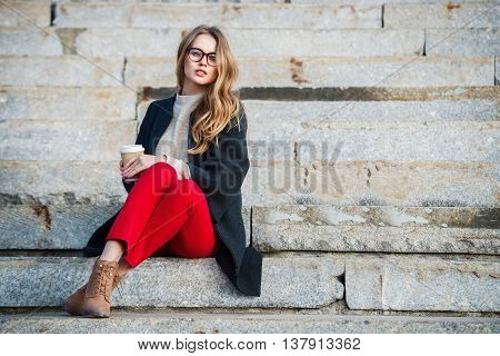 Beautiful gil with coffee cup sitting on outdoors stairs wearing red pants and glasses.