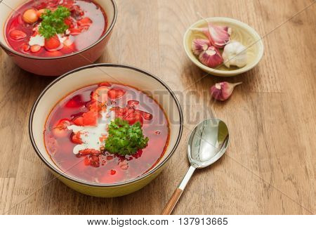 Traditional Ukrainian borsch (vegetable soup) with garlic on wooden background