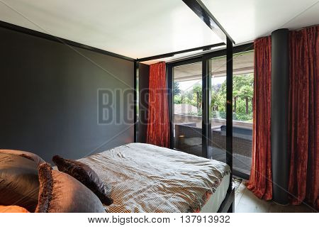 Wooden canopy bed and hardwood floor, black wall