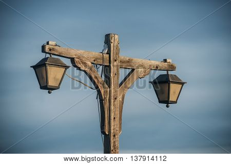 old fashioned wooden street light with two lamps