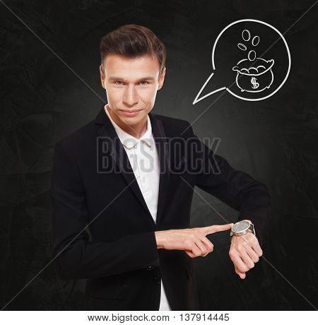 Time is money. Businessman point at his watch showing clock, cash flow concept. Man in suit at black background, thinking cloud with bag of coins. Work and earn, business, finance.