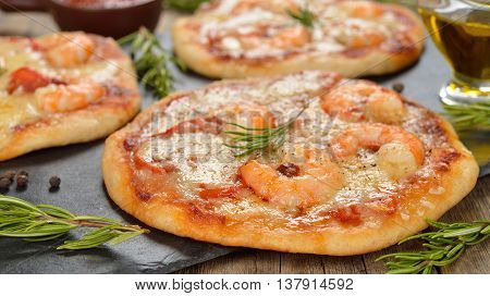 Mini pizza with shrimp and rosemary on a wooden background
