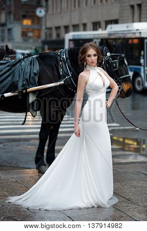 Portrait of beautiful woman bride in long white wedding dress posing in New York City street