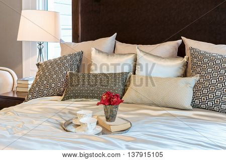 Luxury Bedroom Interior With Brown Pattern Pillows And Decorative Tray Of Flower On Bed