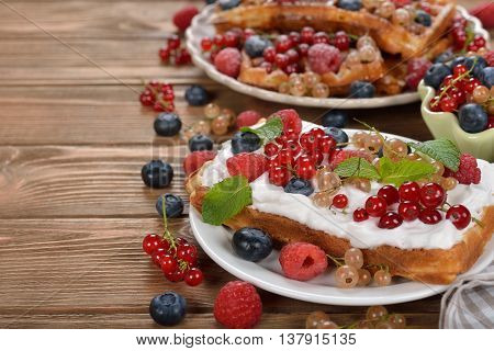 Waffles with whipped cream and berries on a brown background