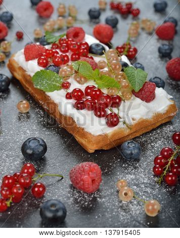 Waffles with whipped cream and berries close up