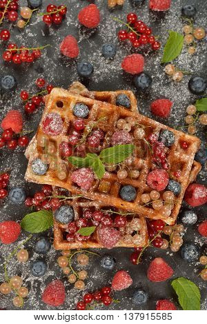 Waffles with berries on a black background