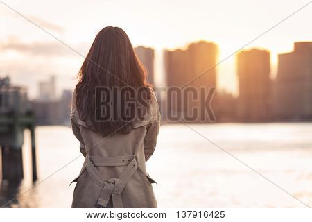 Beautiful lonely girl waiting for somebody bear the water at sunset time