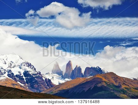 Fabulous harmony of the national park Torres del Paine in Chile. Three rocks Torres are surrounded by picturesque clouds