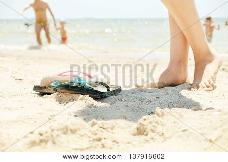 Summer background. Female legs and beach slippers on the white sand at the beach on a sunny day on the background of the sea