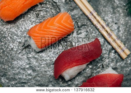 Close-up of fresh delicious sushi on board with chopsticks.From above