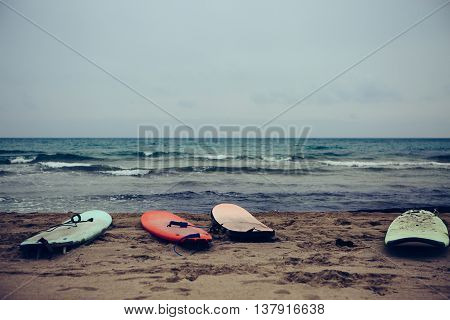 View on abandoned surfboards on beach against of wavy seascape
