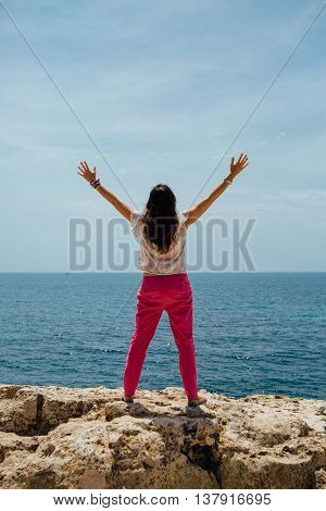 back view of adult brunette with outstretched arms greeting sea. Copy space area available