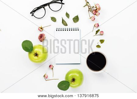 sketchbook with cup coffee green apples with leaves dry rose flowers and glasses. Flat lay top view