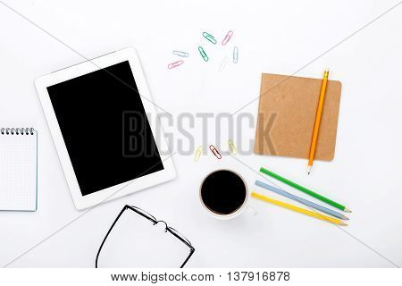 Design workspace. tablet notebook colored pencils paper clips glasses and cup of black coffee on a white background. top view flat lay