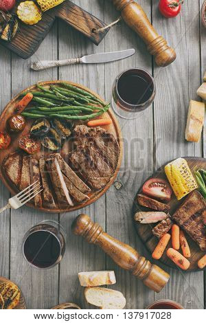 Juicy steak cooked on a grill with grilled vegetables and red wine on wooden table top view. Outdoors food concept