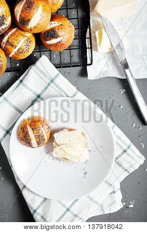 Top view of homemade baked sliced pretzel bun with poppy seeds and butter on it on white plate. Pretzel bun is german cuisine dish, ideal for lunch or breakfest with butter and tea.