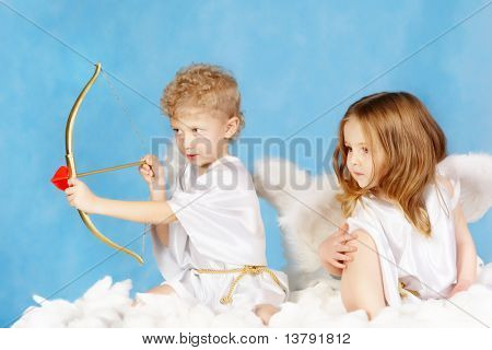 Portrait of two cute cupids sitting on the cloud