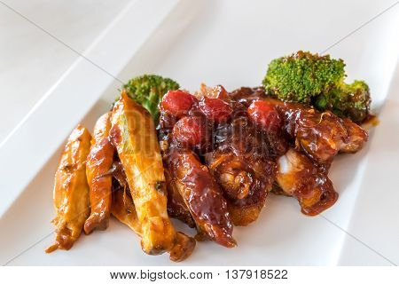 Pork Rib Grilled and Fried Potato Wedges on White Plate with Sauce and Veggies, Gourmet cuisine.