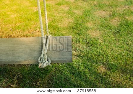 Wooden swing in a playground area for recreation.
