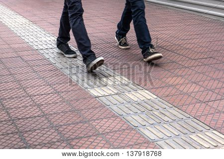 two people in jeans go on the sidewalk