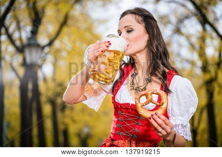 Girl in traditional Bavarian Tracht drinking beer out of a huge mug, holding pretzel in other hand