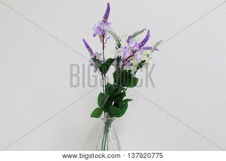 Plastic flowers in a vase on a dark gray background
