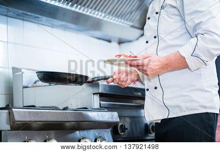 Chef with pan in restaurant kitchen