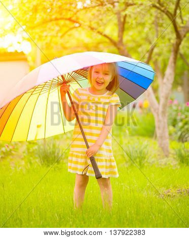 Portrait of a smiling little girl staying on green grass under the colorful umbrella. Cute child enj