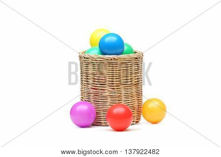 Colorful plastic balls in a wooden basket